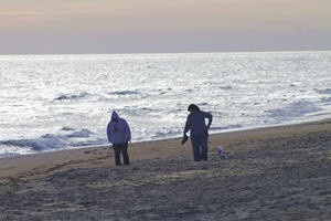Couple waking on beach in winter