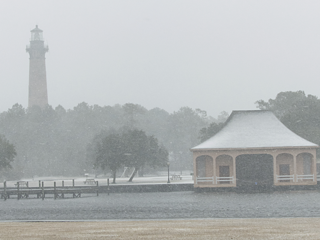 Whalehead Club boathouse with the Currituck Beach Lighthouse in the snow.