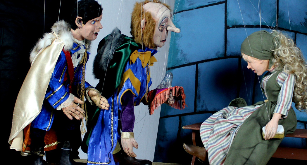 Offering the glass slipper to Cinderella in the Columbia Marionette Theatre production.