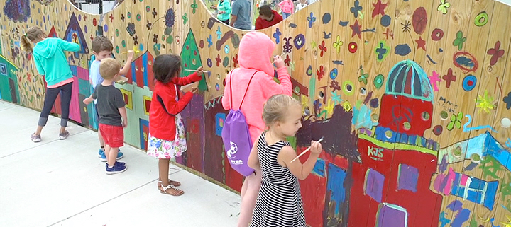Kids painting the wall at Dowdy Park at Artrageous 2017.