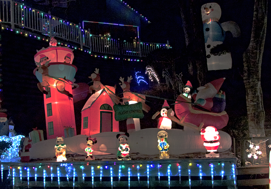 """""""And away they all flew like the down of a thistle."""" Santa and his reindeer take to the skies at the Poulos Christmas lights display."""