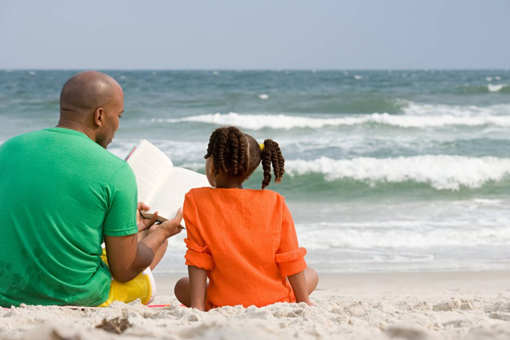 Father and Daughter reading on the beach in the Outer Banks.
