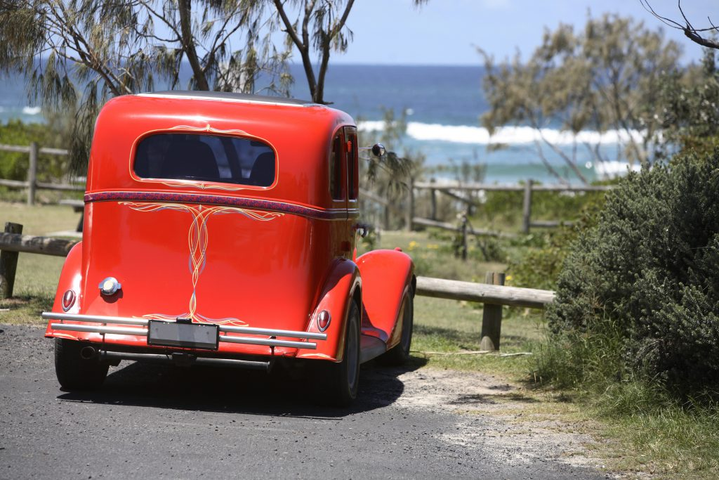 Red hot rod parked at a beach access overlooking the atlantic ocean.