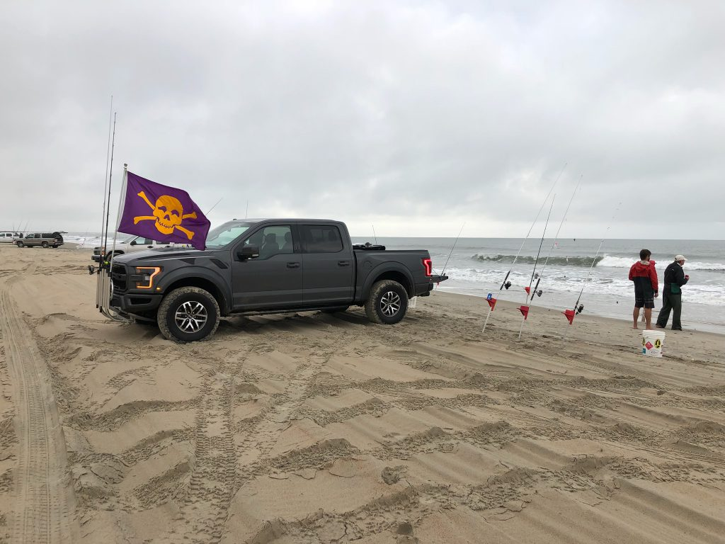 truck on beach with surf fishermen