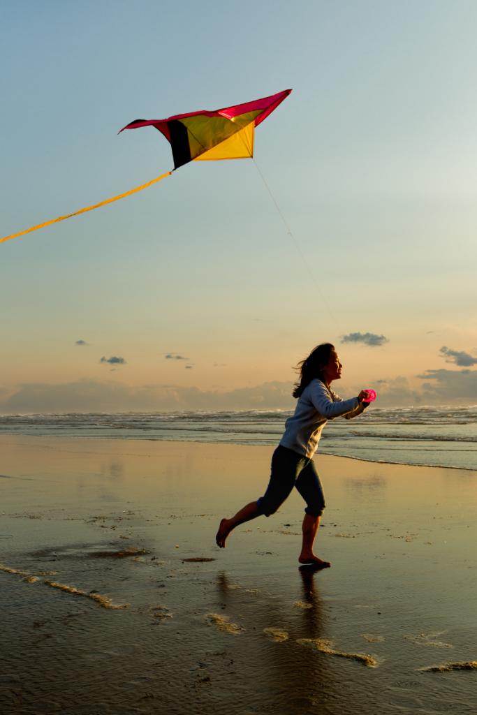 Child girl running on beach flying a kite