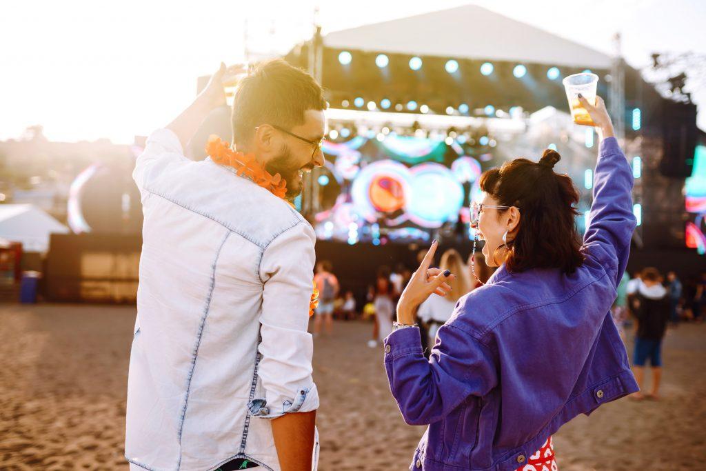 A man and woman enjoying music at an outdoor concert.