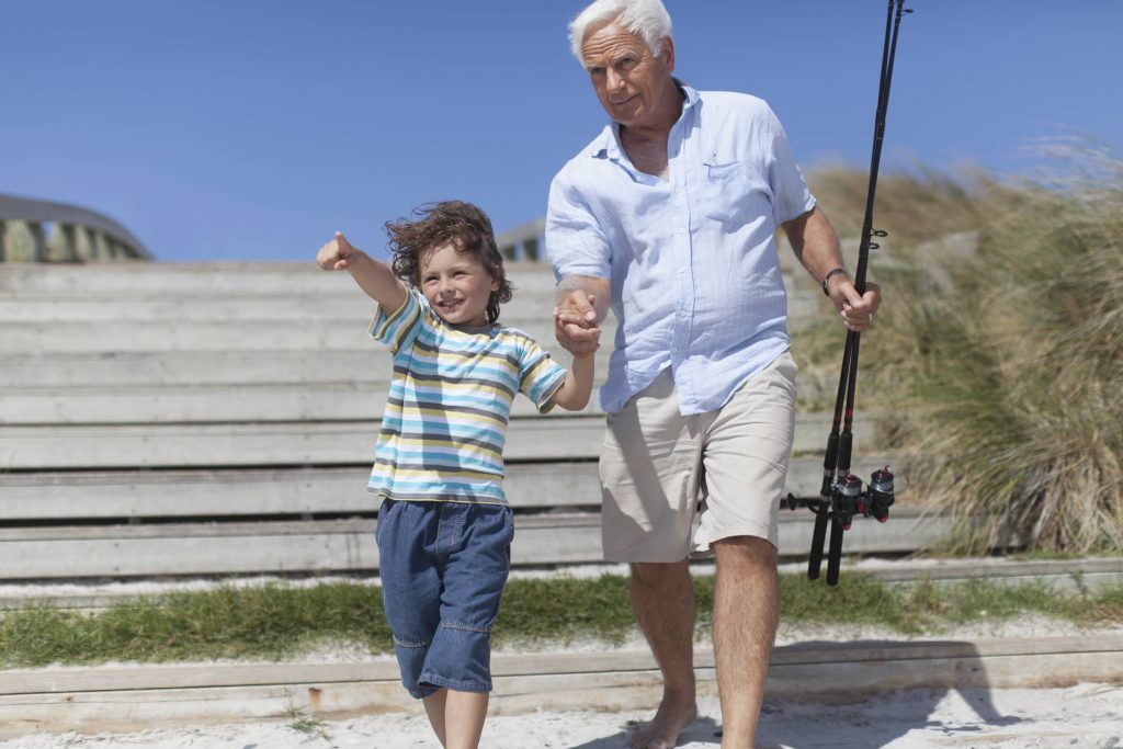 Grandfather and grandson fishing on beach