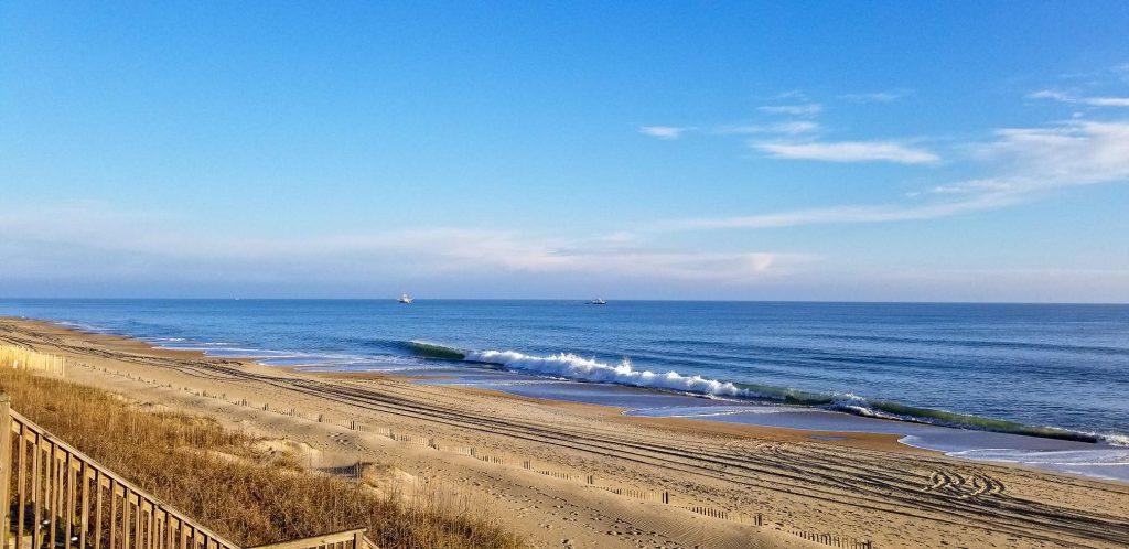 sand, wooden stairs, railings, atlantic ocean, waves, blue skies, sand dunes, boat in distance, soft clouds in sky