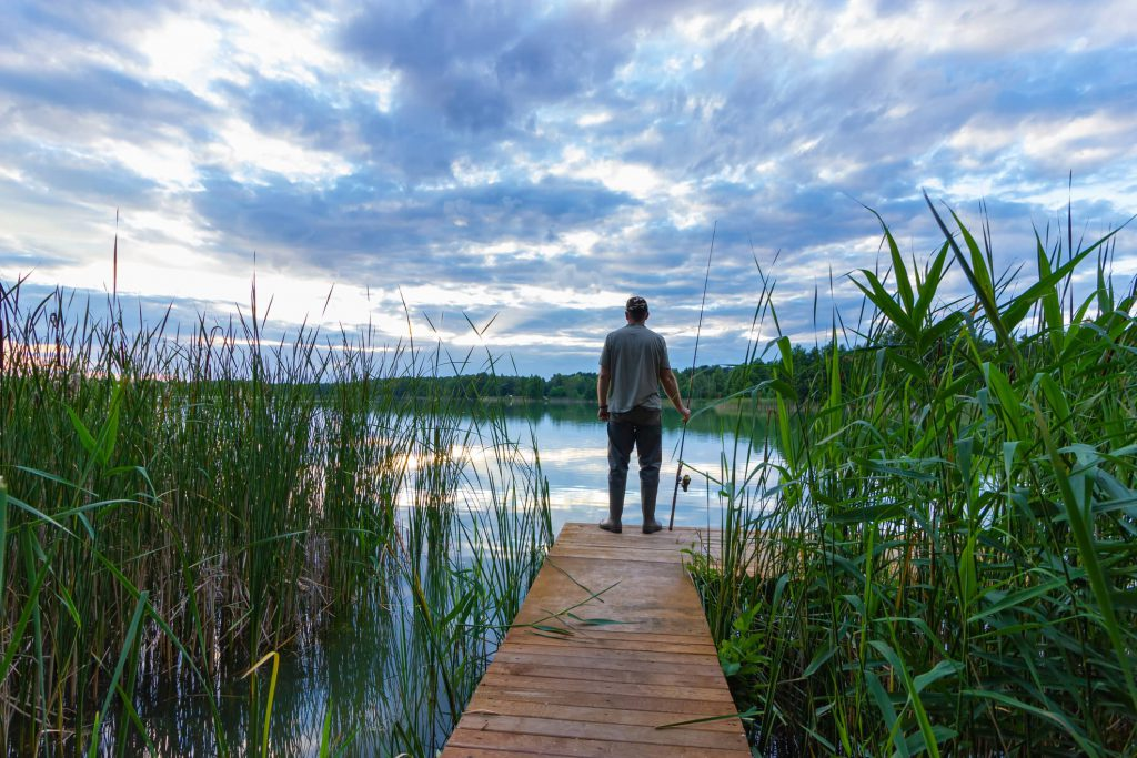 A man standing in the reeds fishing in the sound