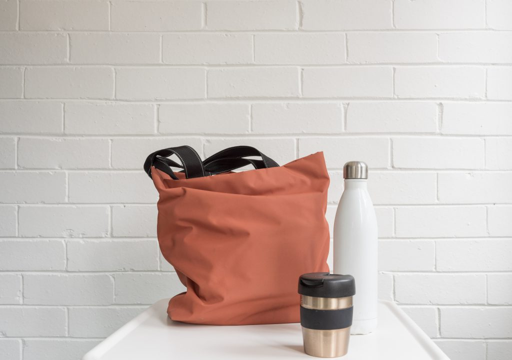 reusable coral bag, white water bottle, white brick wall in background, silver and black tumbler, white countertop