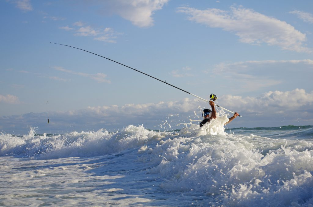 Sea fishing, surf fishing, fisherman into the waves try to cast the line
