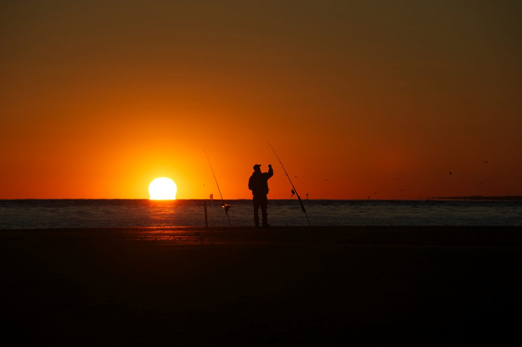 A fisherman is silhouetted by a sunset on a beach in North Carolina as he gets a rod ready to cast out. Birds can be seen flying in the background